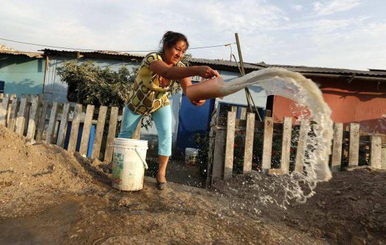 Mulher retira água suja de sua casa em Callao, Peru.