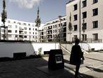 Una mujer para junto a un complejo residencial en Berlín
