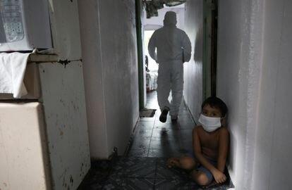 Criança olha para um trabalhador municipal de saúde em Manaus, que sofre novo colapso no sistema de saúde durante a pandemia.