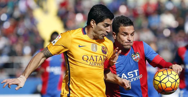 "O zagueiro do Levante ""Toño"" García, à direita, com a bola, ao lado do atacante uruguaio do Barcelona, Luis Suárez."