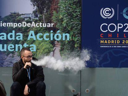 Um homem fuma um cigarro eletrônico na entrada da Cúpula do Clima em Madri.