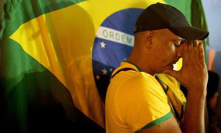 Um torcedor do Brasil reza antes da partida contra o México.