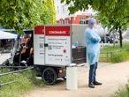 Un sanitario junto a un vehículo donde realizan test rápidos de coronavirus (COVID-19) en Berlín. Imagen de 2021. FOTO: Patricia Sevilla .