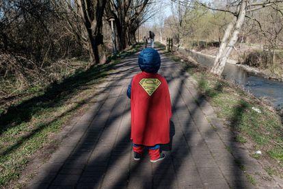 Criança vestida de Super-Homem caminha em em Casalpusterlengo, uma das regiões isoladas na Itália.