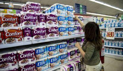 Mulher escolhe papel higiênico em um supermercado de Santiago.