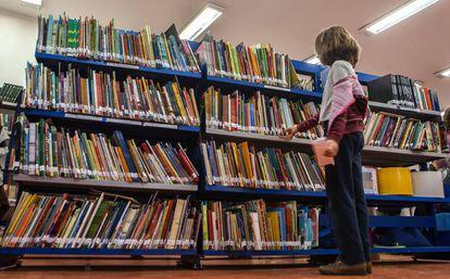 Aluna escolhe livro da biblioteca.