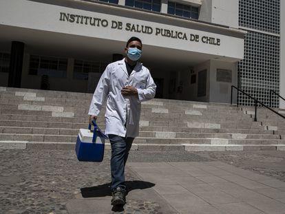 Um trabalhador de saúde caminha em frente ao Instituto Chileno de Saúde Pública, em Santiago, após a autorização do uso da vacina Pfizer.