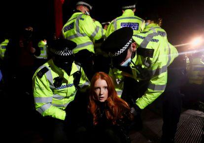 Agentes da Scotland Yard detém uma mulher no sábado, durante uma vigília, em Londres.