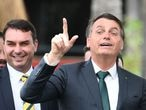 (FILES) In this file photo taken on November 21, 2019 Brazilian President Jair Bolsonaro (R) gestures next to his son, Senator Flavio Bolsonaro, during the launching of his new party, the Alliance for Brazil, at a hotel in Brasilia. - Press organizations in Brazil rejected a judge's decision on September 4, 2020 of prohibiting TV chain Globo the release of documents regarding Flavio Bolsonaro's judicial process for alleged corruption for considering it is under secrecy order. (Photo by EVARISTO SA / AFP)