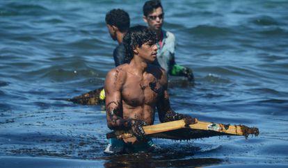 Um rapaz mergulha na água suja de petróleo.