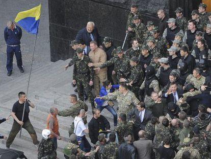 Ativistas entram em confronto com policiais na porta do Parlamento em Kiev.