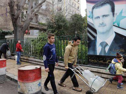 Sírios enchem galões com água numa fonte pública de Damasco, nesta terça.