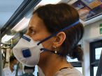 Passengers on the BTS Skytrain wear face masks amid concerns over the spread of the COVID-19 coronavirus in Bangkok on March 20, 2020. (Photo by Lillian SUWANRUMPHA / AFP)