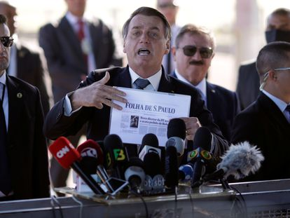 Bolsonaro, com um exemplar do jornal Folha de S.Paulo nas mãos, ameaça jornalistas e manda repórteres calarem a boca, na manhã desta terça-feira, em Brasília.