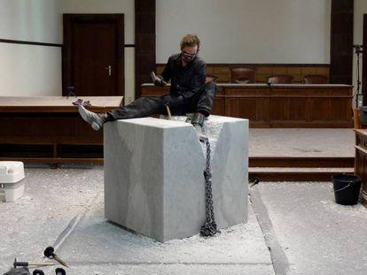 Mikes Poppe luta para escapar do bloco de mármore durante a sua performance.