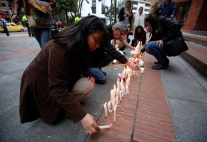 Várias pessoas acendem velas