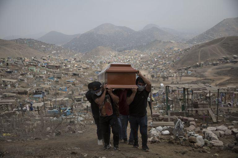 Familiares carregam o caixão de vítima da covid-19 no cemitério Nueva Esperanza, na periferia de Lima, em 2020.