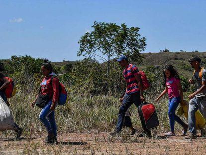 Venezuelanos caminham em Pacaraima, Brasil, depois de cruzar a fronteira.