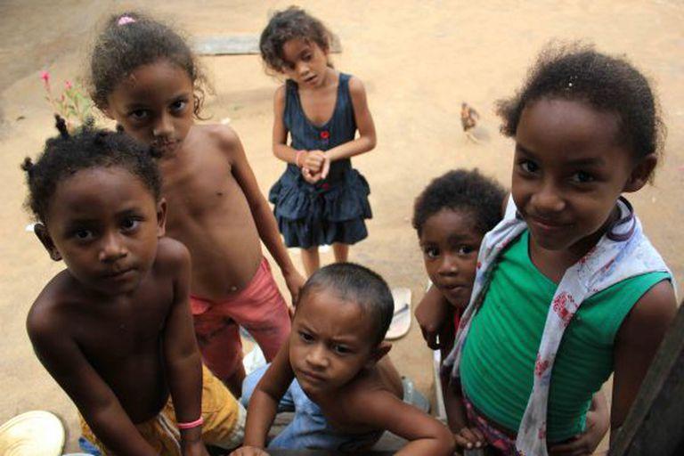 Crianças quilombolas ocupam a escada de uma casa para assistir TV.