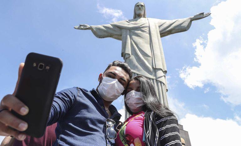 BRA01. RIO DE JANEIRO (BRASIL), 13/03/20.- Los turistas de Maranhão, norte de Brasil, Jardiel do Carmo (izq) y Samara Souza (der), aprovechan la luna de miel para conocer el monumento del Cristo Redentor con mascarillas como protección contra el coronavirus, este viernes, en Río de Janeiro (Brasil). Algunos turistas que visitan por estos días Río de Janeiro comienzan a protegerse del coronavirus y sitios emblemáticos de la ciudad brasileña, como el icónico Cristo del Corcovado, con mascarillas. Aunque las indicaciones de las autoridades sanitarias solo recomiendan el uso de mascarilla a quienes fueron contagiados con la enfermedad y a sus acompañantes permanentes, algunos turistas prefieren utilizarlas en todo momento pese a que ello no represente una real protección, según los expertos. EFE/Antonio Lacerda