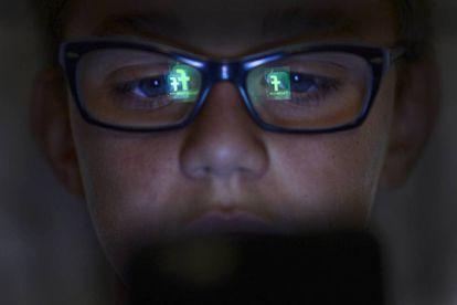 Criança com o reflexo de um smartphone no rosto