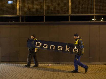 Dois operários retiram o cartaz do Danske Bank na filial de Tallin (Estônia), em 5 de outubro de 2019.
