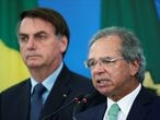Brazil's Economy Minister Paulo Guedes speaks near of the Brazil's President Jair Bolsonaro, during a media statement announcing economic measures, amid coronavirus disease (COVID-19) outbreak, in Brasilia, Brazil, April 1, 2020. REUTERS/Ueslei Marcelino
