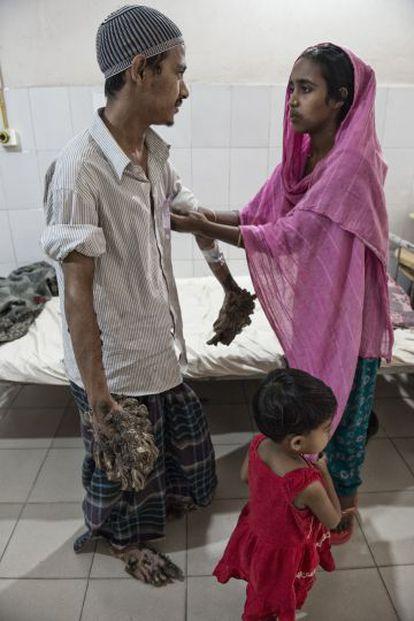 Halima arregaça a manga da camisa de seu marido, que não pode fazer praticamente nada sem ajuda. Ele deseja sentir o toque de sua filha de três anos.