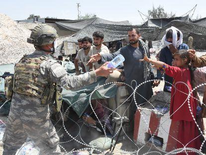 Soldados distribuem água a afegãos acampados na área do aeroporto de Cabul.