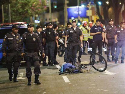 Policiais ao lado do corpo de um homem morto, perto do estádio do Maracanã no dia da cerimônia de abertura.
