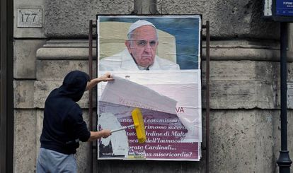 Um operário cobre um cartaz contra o Papa em uma rua de Roma.