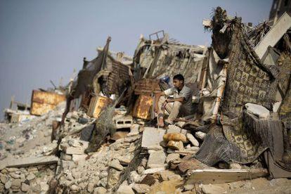 Um palestino sentado nos escombros, em uma praia de Gaza.