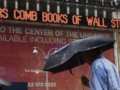 Pedestres na Times Square observam manchetes sobre a crise das subprime, em 2007.
