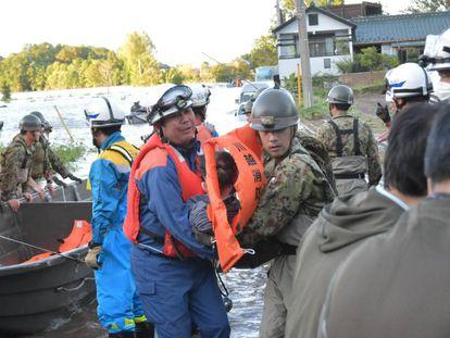 Equipes de resgate retiram moradores de área afetada pelo tufão em Kawagoe.