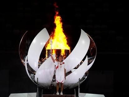 Naomi Osaka segura a tocha olímpica após acender a pira no Estádio Nacional de Tóquio.