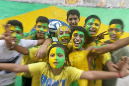 A torcida se pinta com as cores do Brasil.