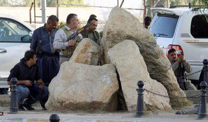 Forças 'peshmergas' curdas abrigadas atrás de pedras nesta sexta-feira em Kirkuk (Iraque).