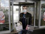 El taxista Rafael Contreras posa con adaptadores para máscaras de bucear y con mascarillas en la entrada del Hospital Infanta Leonor en Leganés.