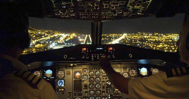 Interior da cabine de comando de um avião durante uma manobra de aproximação.