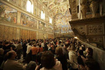 Uma multidão de turistas contempla os afrescos da Capela Sistina.