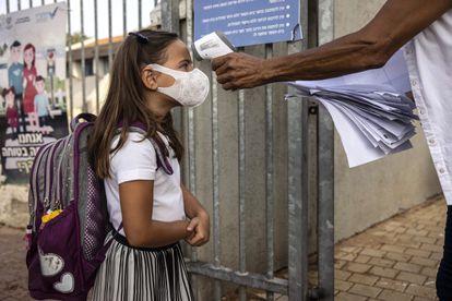 Temperatura de uma estudante é medida em seu primeiro dia de aula em Ashkelon, Israel, em 1º de setembro.