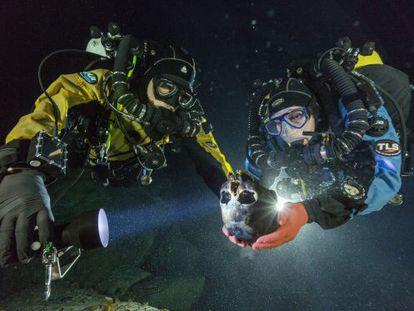 Os mergulhadores Alberto Nava e Susan Bird com o crânio de uma menina de 12.000 anos, descoberto em uma gruta alagada do Yucatán.