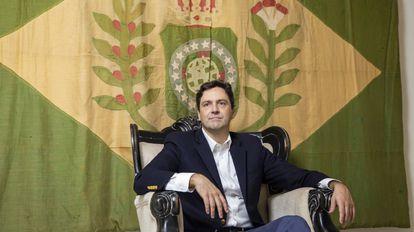 Luiz Philippe de Orléans e Bragança, diante de uma bandeira do período imperial, em seu apartamento.