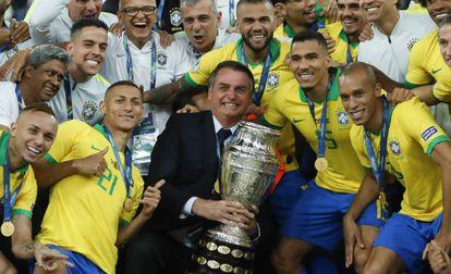 Bolsonaro posa com a taça ao lado dos jogadores da seleção.