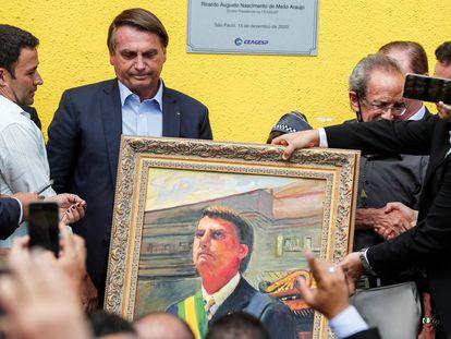 Bolsonaro recebe uma pintura durante visita à Ceagesp, em São Paulo, nesta terça-feira.