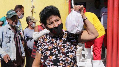 Mulher mostra nesta quarta-feira, 21 de julho, o saco plástico com ossos de boi doados pelo açougue Atacadão da Carne, em Cuiabá (MT).