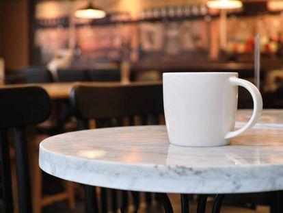 Una taza de café en la mesa de una cafetería.