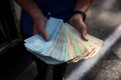 Transportador mostra um maço de bolívares, em 12 de março de 2021, em Caracas.