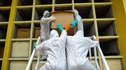 Trabalhadores do cemitério Parques da Paz colocam em uma cova uma caixa de papelão com uma pessoa que morreu supostamente de covid-19, em 20 de abril, em Daule, província de Guayas (Equador).