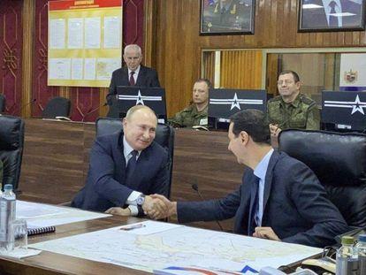 Vladimir Putin e Bashar al-Assad se cumprimentam nesta terça-feira em Damasco.